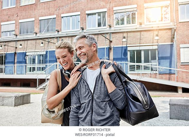Portrait of mature man and young woman with sports bag in front of gym