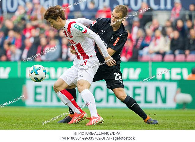 04 March 2018, Germany, Cologne: Soccer, Bundesliga, 1. FC Cologne vs. VfB Stuttgart at RheinEnergieStadion: Cologne's Yuya Osako (L) and Stuttgart's Holger...