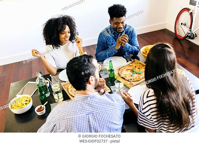 Group of friends having a pizza at home