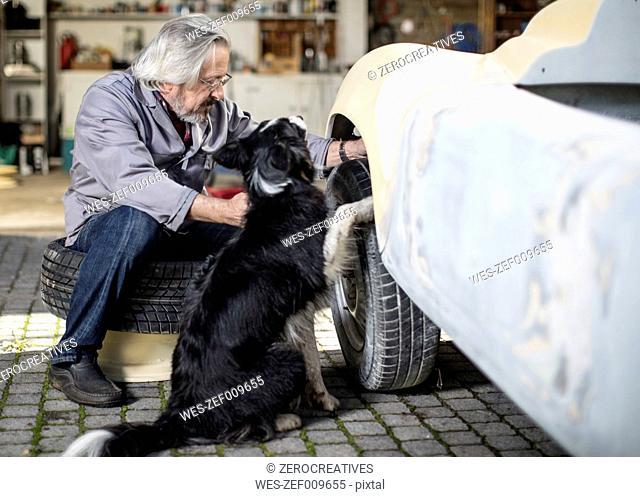 Senior man with dog examining car tyre