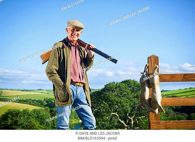 Caucasian man with shotgun and rabbits in rural field