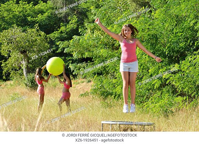 Girl jumping on trampoline at field
