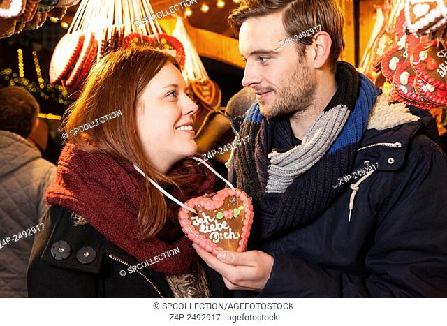couple with german gingerbread heart on christman market