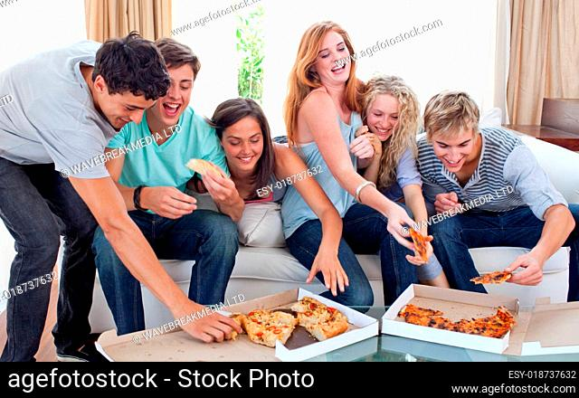 Friends eating pizza at home