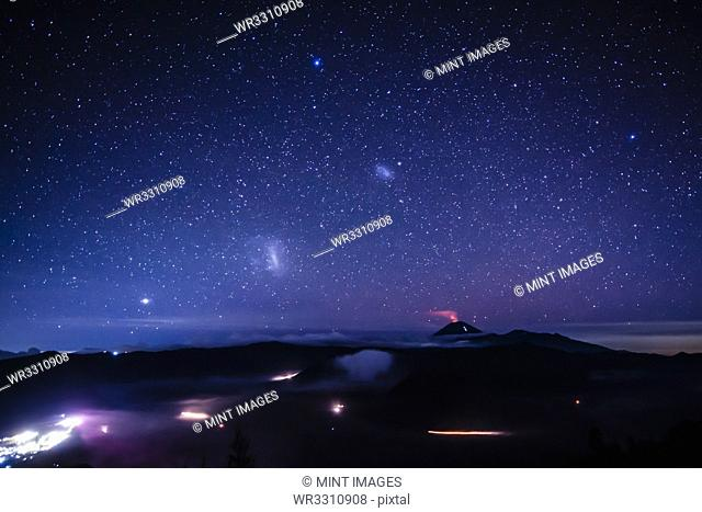 Starry night sky over active volcano