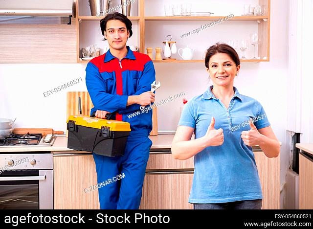 The young male repairman repairing tap