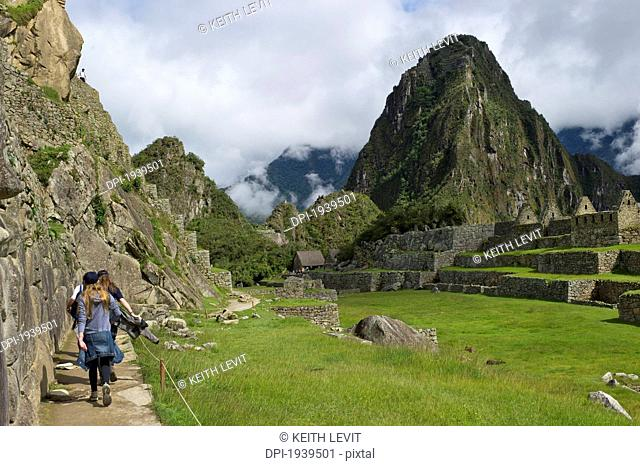 girls walking through machu picchu, peru