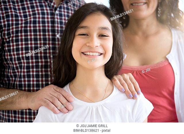 Hispanic girl smiling with parents