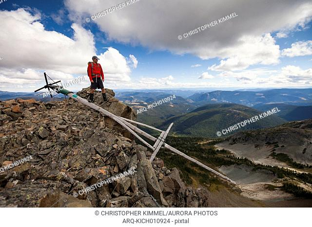 A climber stands on the summit of Jim Kelly Peak, beside an old mast that was historically used for a weather station