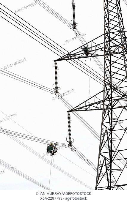 Maintenance work being done on high voltage electricity cables from Sizewell nuclear power station viewed from below looking up towards a pylon, Suffolk