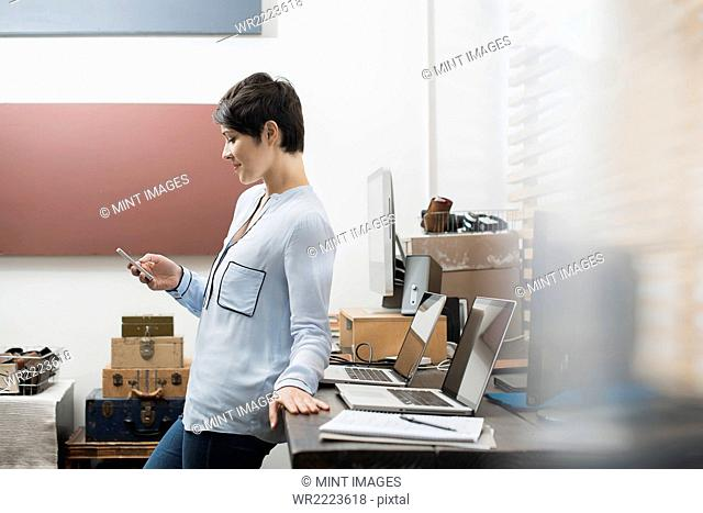 A woman in a home office with a desk with two laptops, checking her smart phone