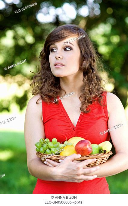 Young woman holding basket filled mix fruit, Debica, Poland
