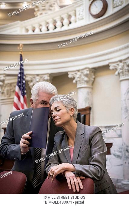 Caucasian politicians whispering in capitol building