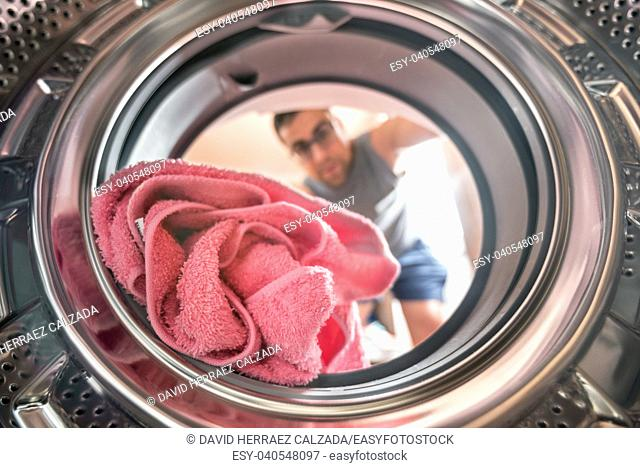Young man doing laundry view from the inside of washing machine