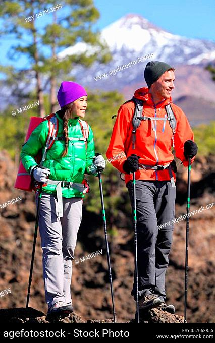 Hikers people hiking - healthy active lifestyle. Hiker couple hiking in beautiful mountain nature landscape. Woman and man hikers walking during hike on volcano...