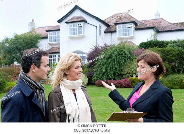Mid adult couple and female estate agent outside house