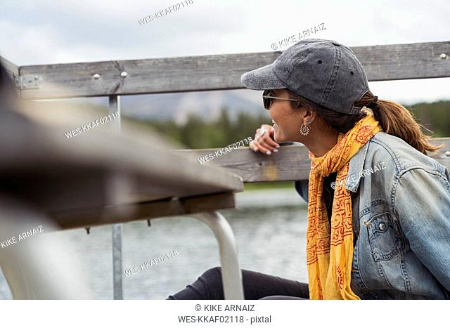 Finland, Lapland, smiling young woman on jetty at the lake