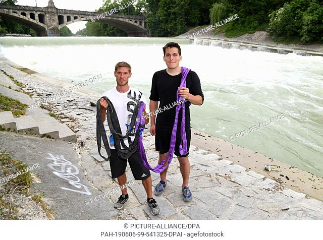 06 June 2019, Bavaria, Munich: The two slackliners Lukas Irmler (l) and Sören Arlt present their belts standing around the banks of the Isar