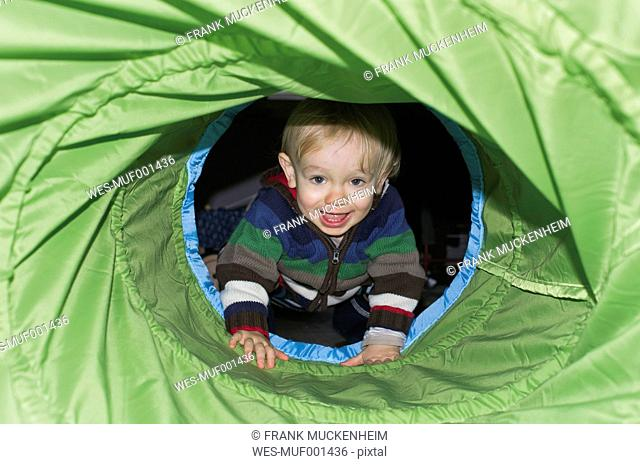 Toddler sitting in play equipment