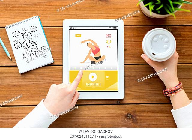 sport, education, technology and people concept - close up of woman with fitness application on tablet pc computer screen, notebook and coffee on wooden table