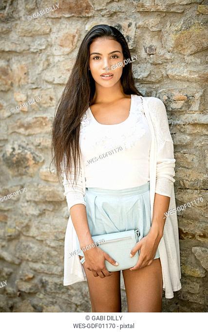 Portrait of fashionable young woman with handbag