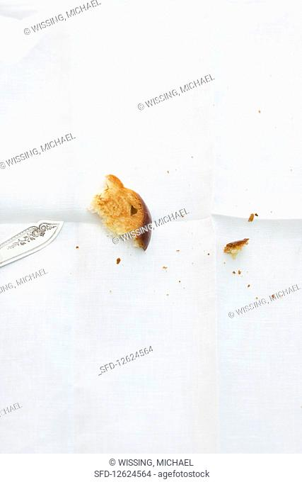 A piece of brioche and crumbs on a white tablecloth