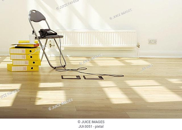 Telephone connected to wooden floor socket on chair beside stack of yellow folders in empty office