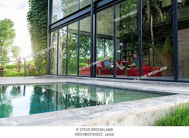 Garden view through glass facade of couple with laptop and book relaxing on red couch in modern design house in front of swimming pool