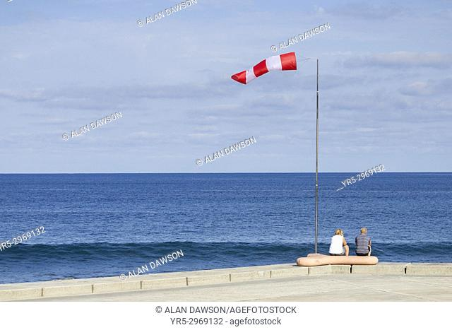 Mature couple sitting under windsock looking out to sea in Las Palmas, Gran Canaria, Canary Islands, Spain