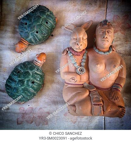 Clay miniatures of two musical instruments with the shape of turtles and a small sculpture of the goddess Ixchel, the rabbit god, hugging a woman