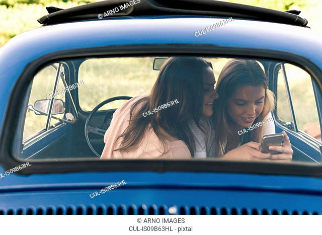 Friends in vintage car looking at smartphone smiling, Firenze, Toscana, Italy, Europe