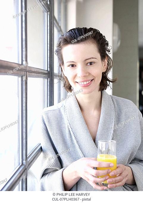 Woman in bathrobe by window drinking