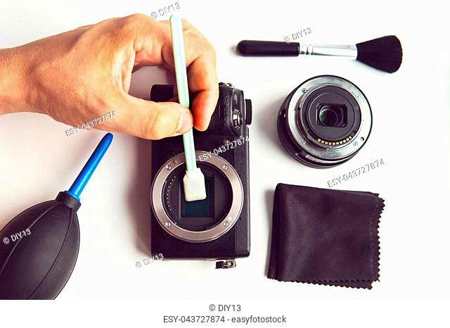 Mirrorless Sensor cleaning and Maintenance,Photographer hand cleaning sensor of camera by using sensor swab and vacuum pump