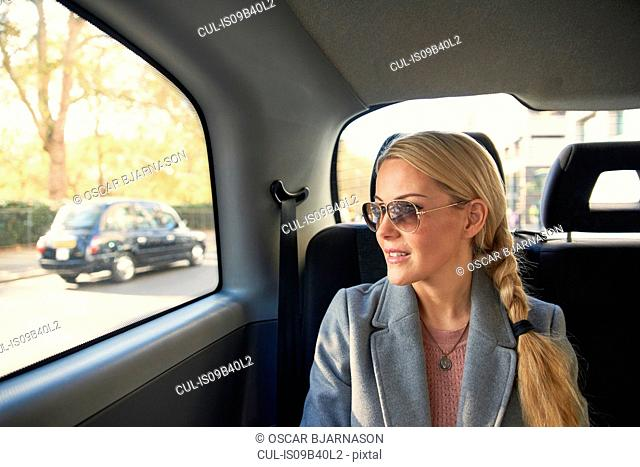 Mid adult woman sitting in back of taxi
