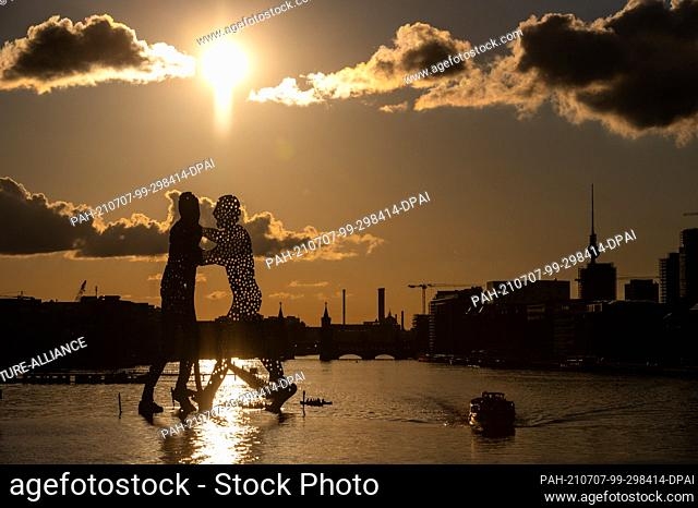 """dpatop - 07 July 2021, Berlin: Paddle boats pass under the sculpture """"""""Molecule Man"""""""" by the American sculptor Jonathan Borofsky as the sun sets on the Spree"""