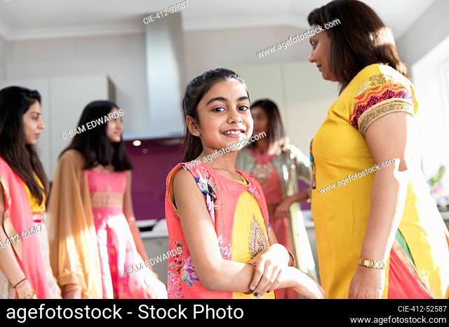 Portrait happy Indian girl in sari with women in kitchen