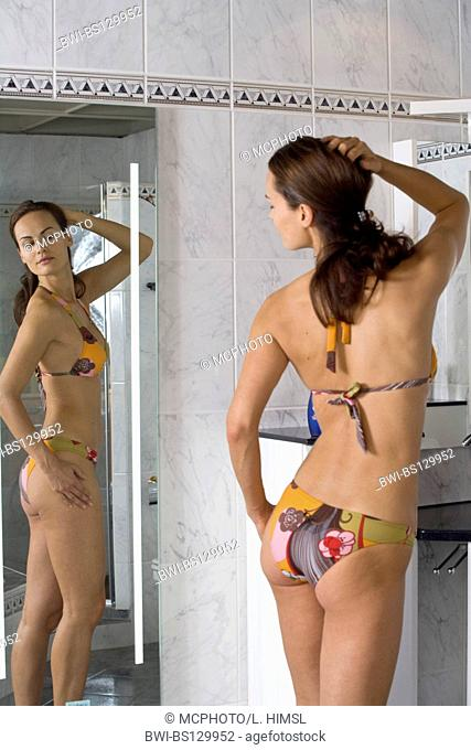 young woman with bikini looks at herself in the mirror
