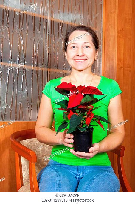 woman with Poinsettia flowers in flowering pot