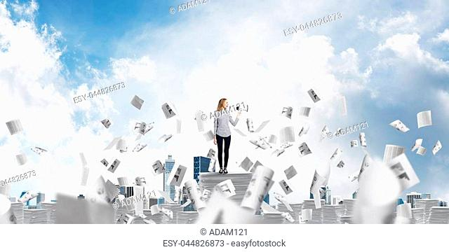 Woman in casual clothing standing among flying papers with speaker in hand and with skyscape on background. Mixed media