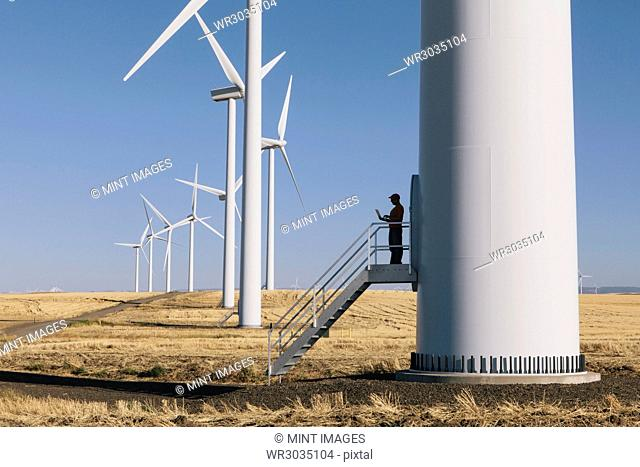 A wind farm technician standing and using a laptop at the base of a turbine on a wind farm in open countryside at Palouse
