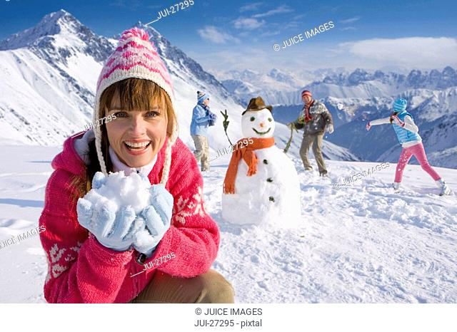 Family building snowman together and having snowball fight