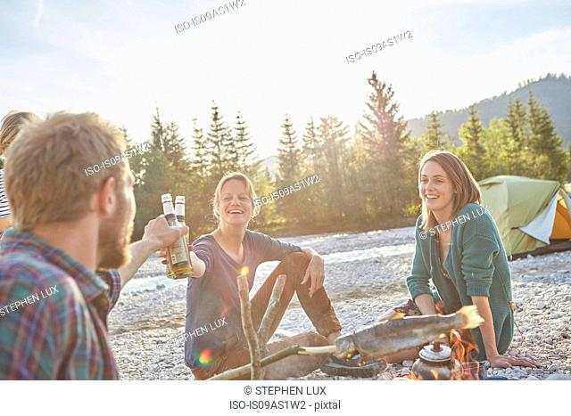 Adults sitting around campfire making a toast with beer bottles