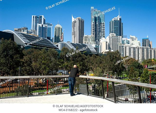 A man looks at Sydney's cityscape of the central business district with the Tumbalong Park in the foreground. Sydney, New South Wales, Australia