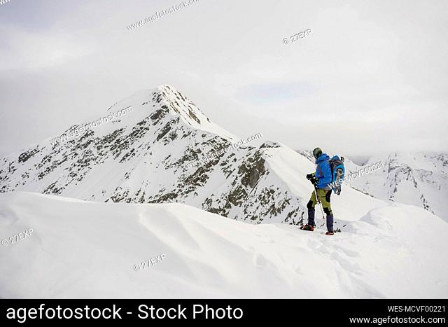Man on an excursion on the crest of a snowy mountain, Lombardy, Valtellina, Italy