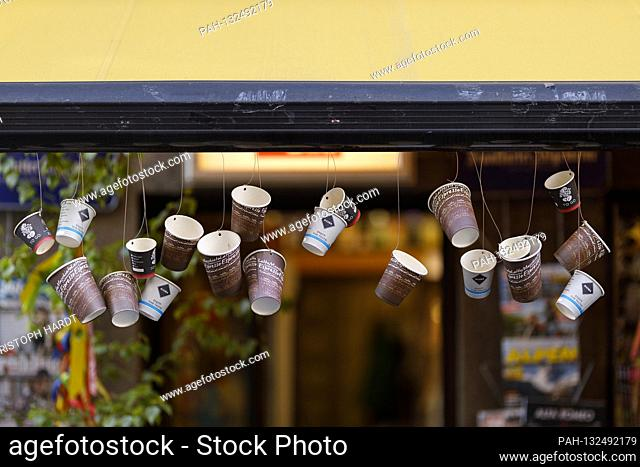 Take-away regulations instead of visiting a restaurant allow the gauze to grow in big cities during the corona crisis, here recycled coffee cups as garlands at...