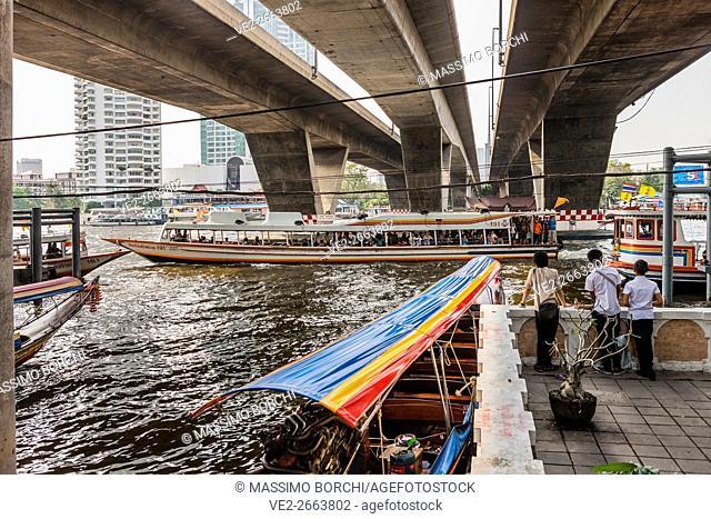 Typical Thai Long Tail boats on Chao Phraya River (Mae Nam Chao Phraya), the Taksin Bridge and the Central Pier (Sathon), Bangkok, Thailand