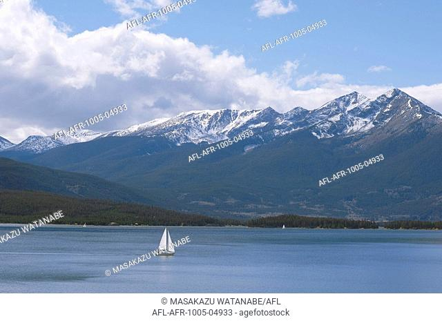 Sail Boat in Lakewater with Mountains in Background