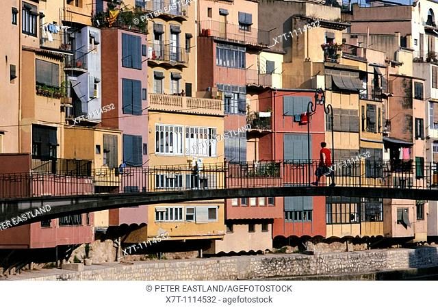 A woman walking across a pedestrian bridge across the River Onyar, in the heart of Girona, backed by a colourful array of multistoried houses