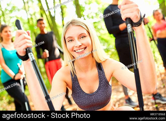 Junge Frau als Fitness Trainer mit Gruppe beim Nordic Walking in der Natur im Sommer