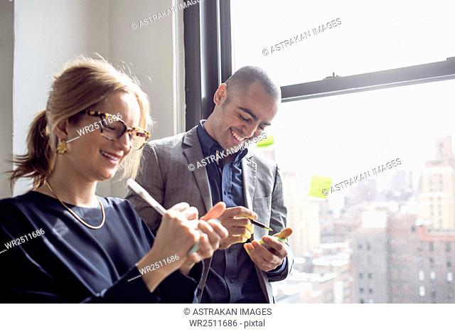 Businessman and businesswoman writing on sticky notes by window